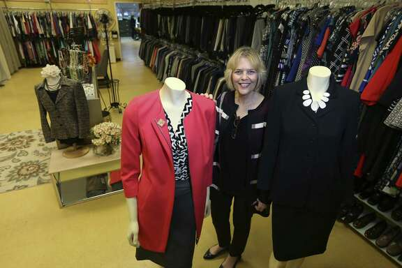 Robbye Floyd, executive director of Dress for Success San Antonio, is shown with a collection of dresses Thursday. The nonprofit also provides clothing for men through its Career Gear program.