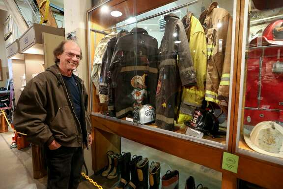 Retired San Antonio Fire Department Lt. Bob Heckman stands beside a display of clothing used by San Antono firefighters in the past at the San Antonio Fire Museum, 801 E. Houston.