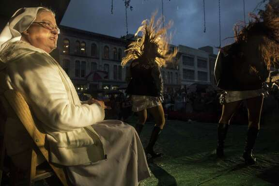 Sister Mary Mullaly of the Salesian Sisters of St. John Bosco watches the Spurs' Silver Dancers perform in the rain during the 31st Annual H-E-B Christmas Tree Lighting Celebration at Alamo Plaza in San Antonio, Texas on November 27, 2015.