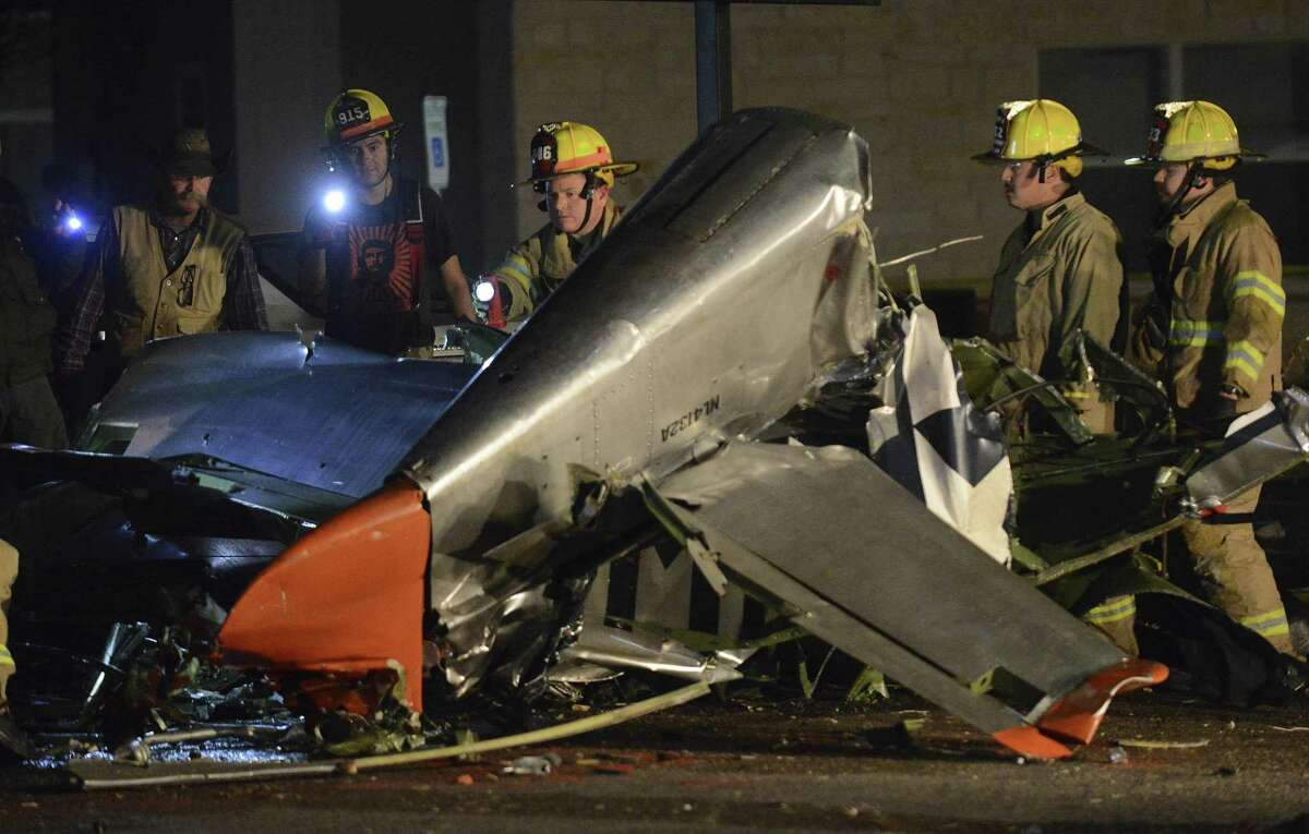 Firefighters and investigators look over the remains of a vintage World War II P-51 Mustang aircraft that crashed into an apartment complex parking lot in Fredericksburg, killing the two occupants of the airplane on Saturday, Nov. 17, 2018.