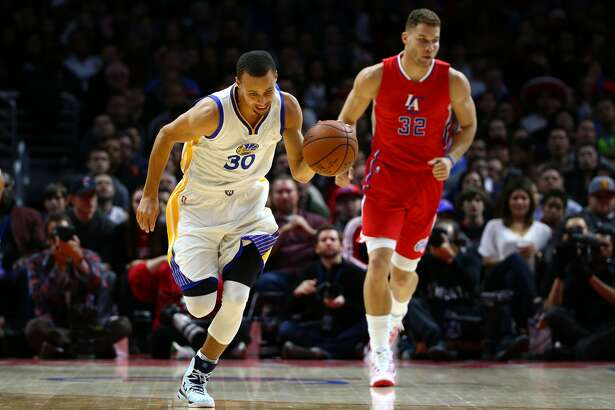 LOS ANGELES, CA - DECEMBER 25: Stephen Curry #30 of the Golden State Warriors starts the fast break upcourt as Blake Griffin #32 of the Los Angeles Clippers looks on during the NBA game at Staples Center on December 25, 2014 in Los Angeles, California. The Clippers defeated the Warriors 100-86. NOTE TO USER: User expressly acknowledges and agrees that, by downloading and/or using this photograph, user is consenting to the terms and conditions of the Getty Images License Agreement. Mandatory copyright notice. (Photo by Victor Decolongon/Getty Images)