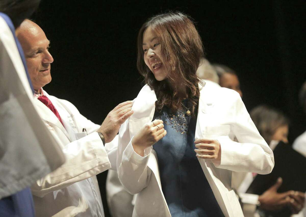 Denise Zheng smiles after receiving her coat as part of the McGovern Medical School's White Coat Ceremony at the Hobby Center on Thursday, Aug. 2, 2018, in Houston. The UT medical school inducted 240 students into its class of 2022.