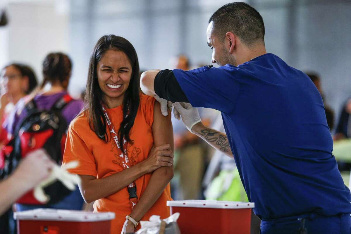Baylor College of Medicine resident Rachna Patel, left, reacts as she receives a flu shot from Occupational Health Medical Assistant Nick Elizondo as hundreds of BCM employees wait to get their free vaccinations before the start of the flu season Thursday Sept. 20, 2018, in Houston