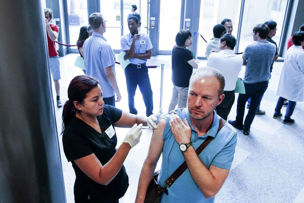 Baylor College of Medicine assistant professor Trent Watkins, right, receives a flu shot from Certified Medical Assistant Rebecca Slappey as hundreds of BCM employees wait to get their free vaccinations before the start of the flu season Thursday, Sept. 20, 2018, in Houston.