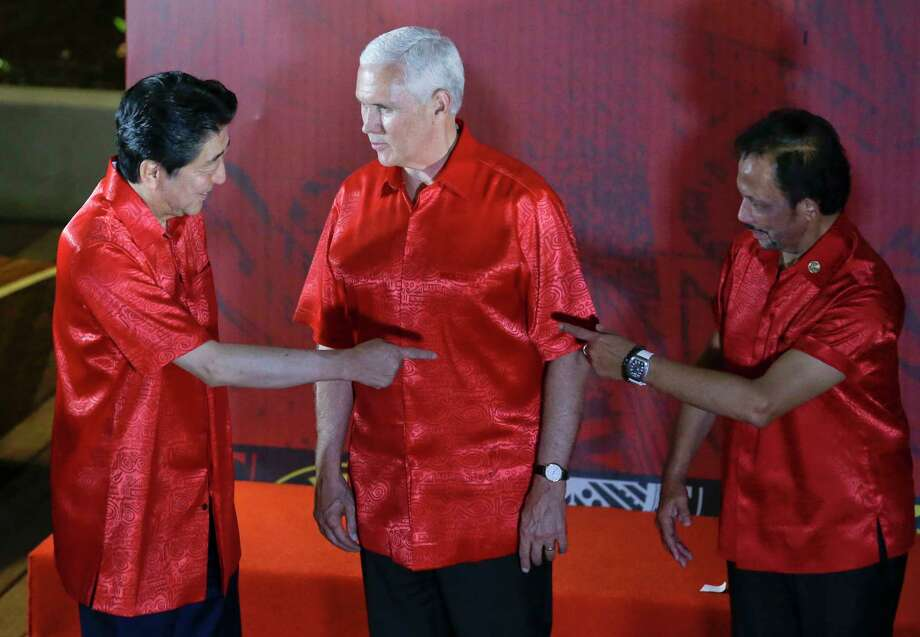U.S. Vice President Mike Pence, center, watches Japanese Prime Minister Shinzo Abe, left, and Brunei Sultan Hassanal Bolkiah gesture before the start of the gala dinner family photo at the APEC summit in Port Moresby, Papua New Guinea, Saturday, Nov. 17, 2018. (AP Photo/Aaron Favila) Photo: Aaron Favila / Copyright 2018 The Associated Press. All rights reserved.