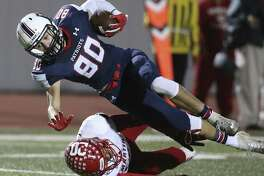 Patriot receiver Robert Garcia goes over Mark Carreon for a first down as Veterans Memorial hosts Laredo Martin in first round playoff action at Rutledge Stadium on November 17, 2018.