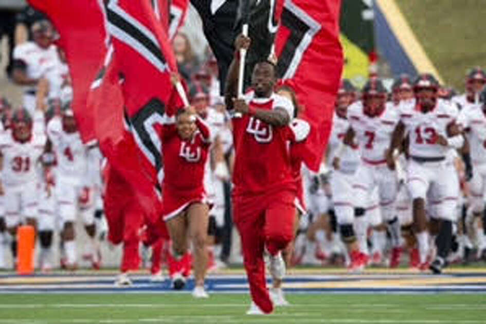 The Cardinals are lead on the field by the cheerleaders before of the start of their Southland Conference matchup against McNeese at Cowboy Stadium in Lake Charles, La., Saturday, Nov. 17, 2018. (Rick Hickman/Special to the Enterprise.)