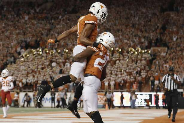 AUSTIN, TX - NOVEMBER 17: John Burt #1 of the Texas Longhorns celebrates with Keaontay Ingram #26 after a second quarter touchdown against the Iowa State Cyclones at Darrell K Royal-Texas Memorial Stadium on November 17, 2018 in Austin, Texas. (Photo by Tim Warner/Getty Images)