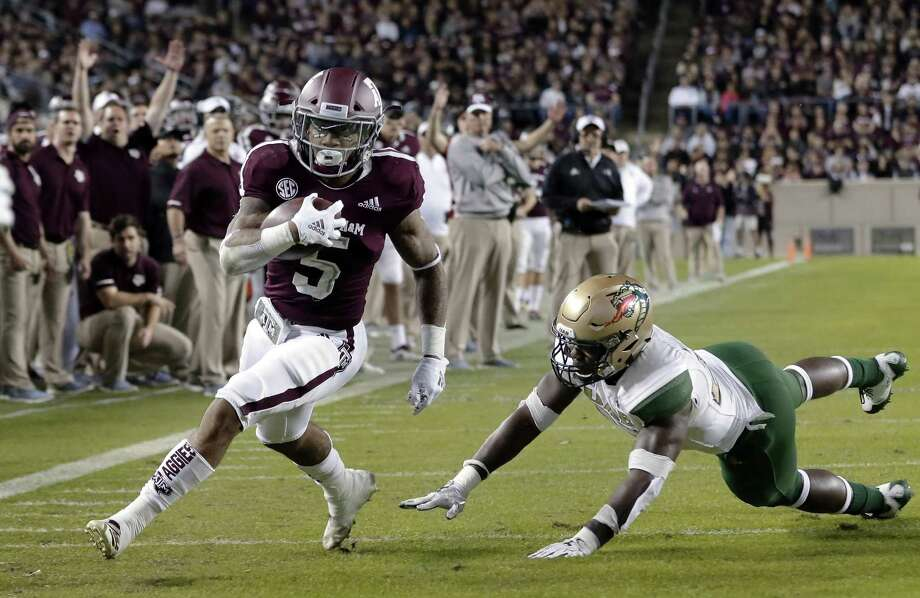 Texas A&M running back Trayveon Williams (5) dodges the tackle attempt by UAB linebacker Chris Woolbright, right, to score during the first half of an NCAA college football game Saturday, Nov. 17, 2018, in College Station, Texas. (AP Photo/Michael Wyke) Photo: Michael Wyke, FRE / Associated Press / Copyright 2018 The Associated Press. All rights reserved.