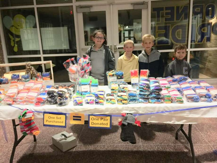 Lillian Flathers, from left, Gage Ratliff, Derek Belloni and Zack Belloni  man the sock table at Carver Center Photo: Courtesy Photo