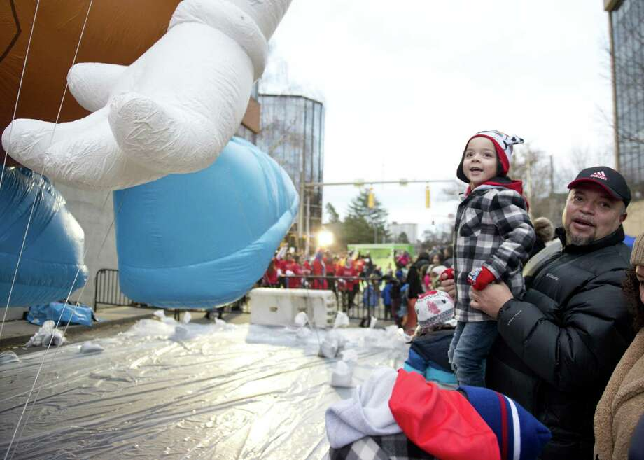 Mathew Rito, 4, and his dad, Julio, of White Plains, N.Y., look at the balloons during the Point72 Giant Balloon Inflation Party, a precursor to the Stamford Downtown Parade Spectacular, in Stamford on Saturday. Photo: Lindsay Perry / For Hearst Connecticut Media / Stamford Advocate Freelance