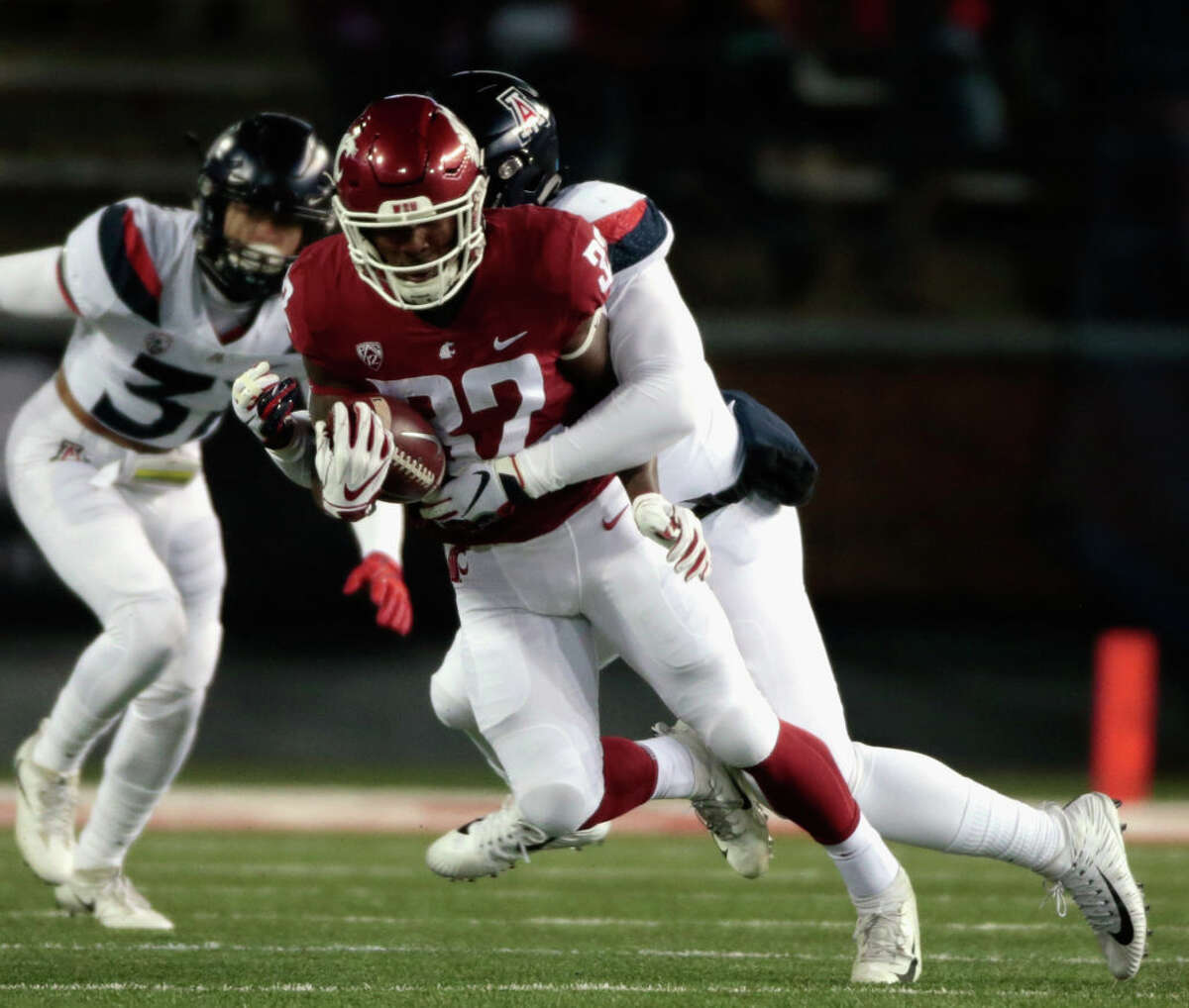 PULLMAN, WA - NOVEMBER 17: James Williams #32 of the Washington State Cougars moves the ball against J.B. Brown #12 of the Arizona Wildcats in the first half at Martin Stadium on November 17, 2018 in Pullman, Washington. (Photo by William Mancebo/Getty Images)