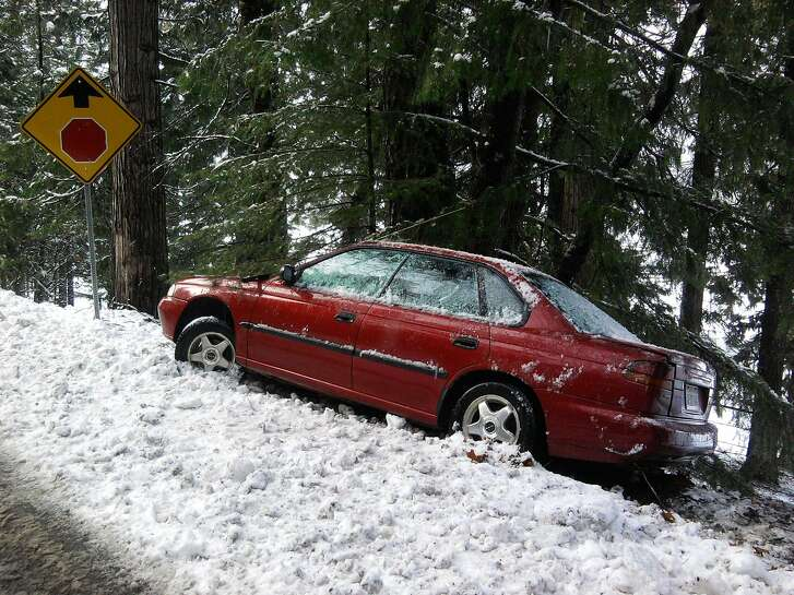 On two-lane country road in Lake Tahoe Basin, this compact car spun out, braking too hard at low speed down hill on ice as it approached stop sign -- creating too much torque for tires to hold traction -- and ended up in the snow bank