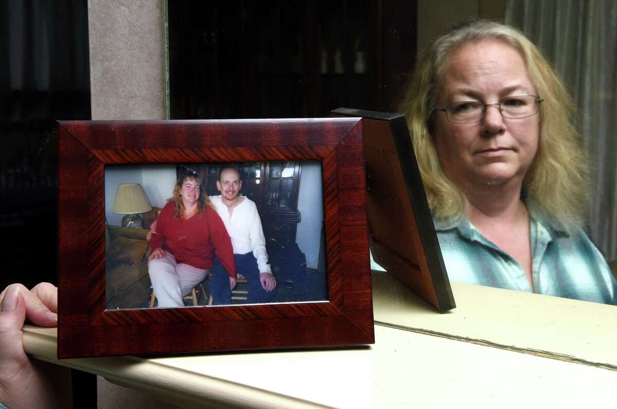 Susan Tendler looks at a photograph of her deceased husband, Harris, and herself at her home in Hamden on November 15, 2018. Harris was killed on December 11, 2016 when he was hit by a car on Dixwell Avenue.