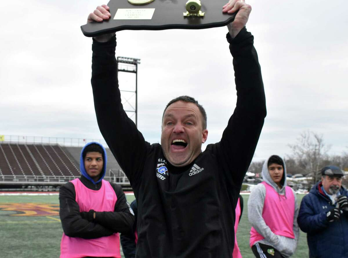Glastonbury coach Mark Landers holds up the plaque after Glastonbury beat Hall 1-0 in the Class LL boys soccer championship at Willbowbrook Park in New Britain on Sunday, November 18, 2018. Landers will coach the Glanstonbury girls program. (Pete Paguaga, Hearst Connecticut Media)