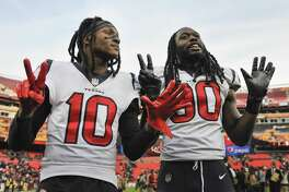 Houston Texans wide receiver DeAndre Hopkins (10) and outside linebacker Jadeveon Clowney (90) hold up seven fingers signaling the Houston's seven straight wins after an NFL football game between the Houston Texans and the Washington Redskins, Sunday, Nov. 18, 2018 in Landover, Md. The Texans defeated the Redskins 23 - 21. (AP Photo/Mark Tenally)