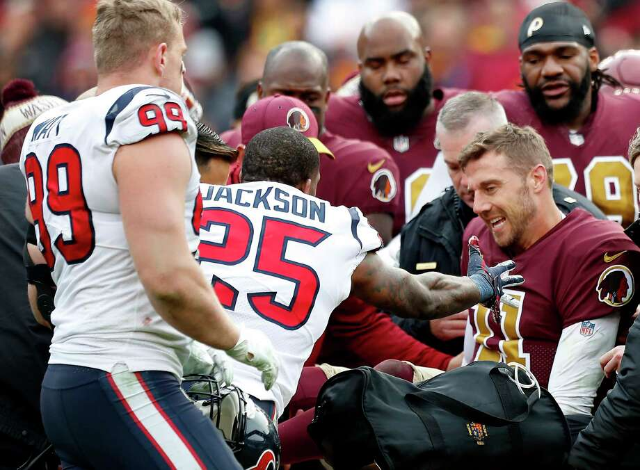 Houston Texans strong safety Kareem Jackson (25) and defensive end J.J. Watt (99) reach out to Washington quarterback Alex Smith (11) as he is carted off the field after suffering a broken leg during the third quarter of an NFL football game at FedEx Field on Sunday, Nov. 18, 2018, in Landover, Md. Photo: Brett Coomer, Staff Photographer / © 2018 Houston Chronicle