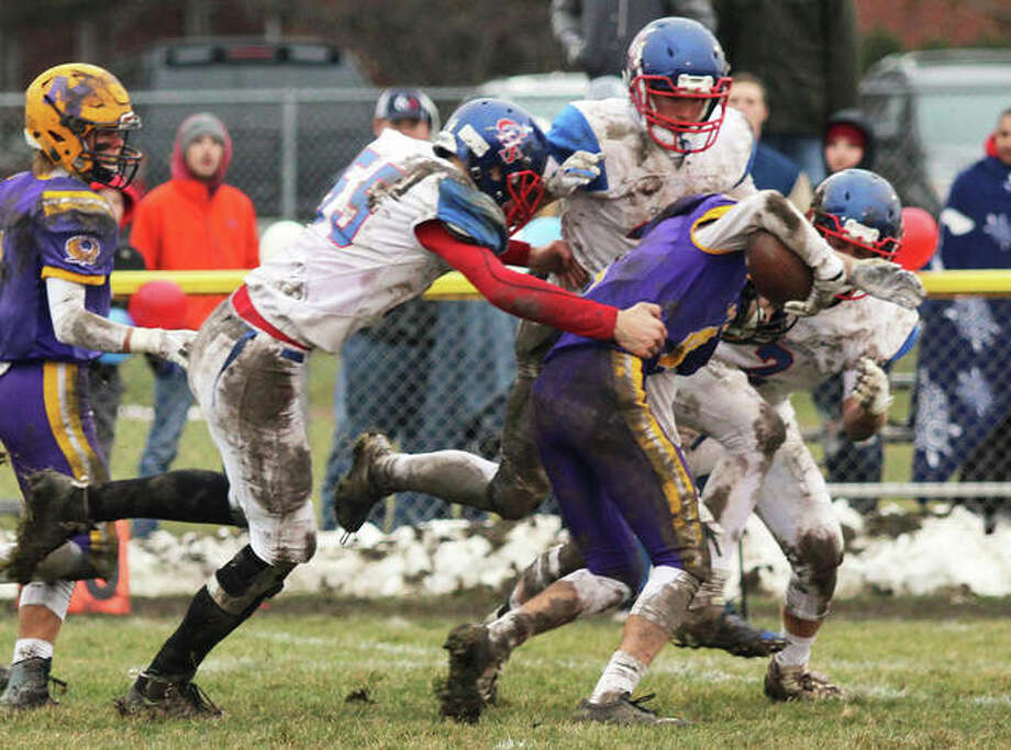 Carlinville's (from left) Logan Rosentreter, Kyle Dixon and Colton DeLong take down Monticello's Luke Stringer (middle) after a 30-yard pass reception in the second half Saturday in a Class 3A semifinal game in Monticello. Photo: Greg Shashack / The Telegraph