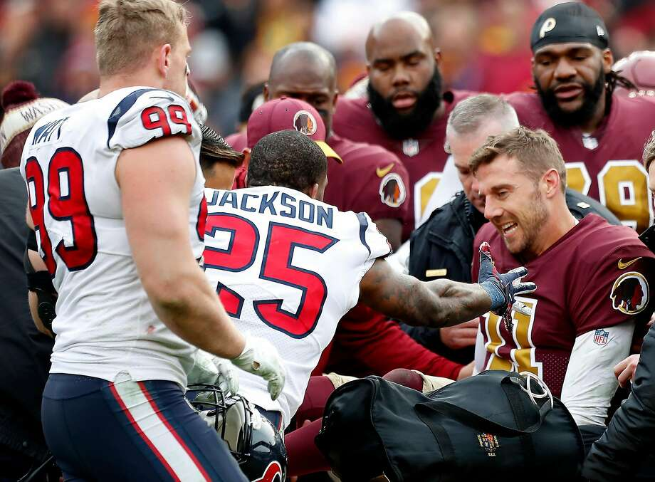 Houston Texans strong safety Kareem Jackson (25) and defensive end J.J. Watt (99) reach out to Washington quarterback Alex Smith (11) as he is carted off the field after suffering a broken leg during the third quarter of an NFL football game at FedEx Field on Sunday, Nov. 18, 2018, in Landover, Md. Photo: Brett Coomer / Staff Photographer