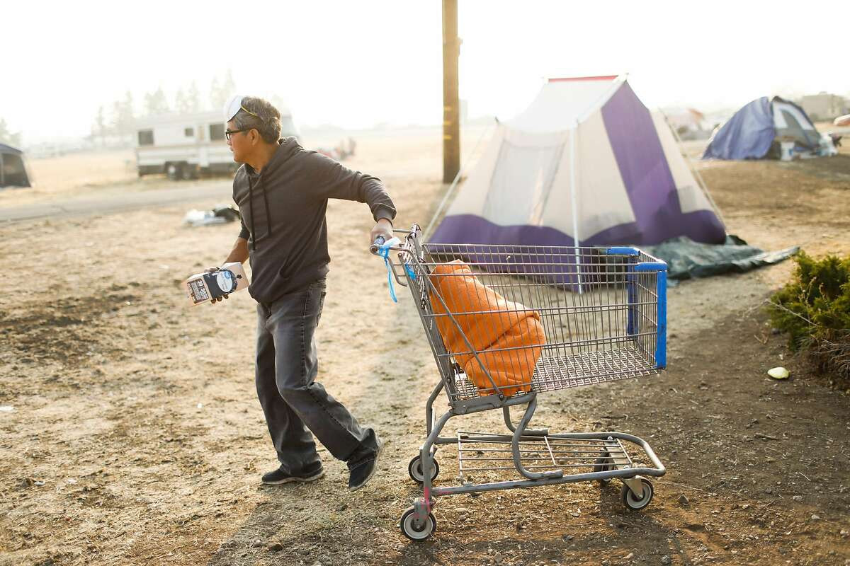 Evacuee Pete Pingul gets his belongings together as he gets ready to leave a makeshift evacuation site at Walmart following the Camp Fire in Chico, California, on Sunday, Nov. 18, 2018.