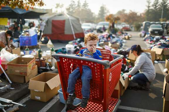 Evacuee Josaiah Darby, 3, waits in a shopping cart as his mother Autumn Darby (right) looks through items at the Target parking lot in Chico, California, on Sunday, Nov. 18, 2018. Autumn and her son Josaiah lost their home after the Camp Fire tore through Paradise.