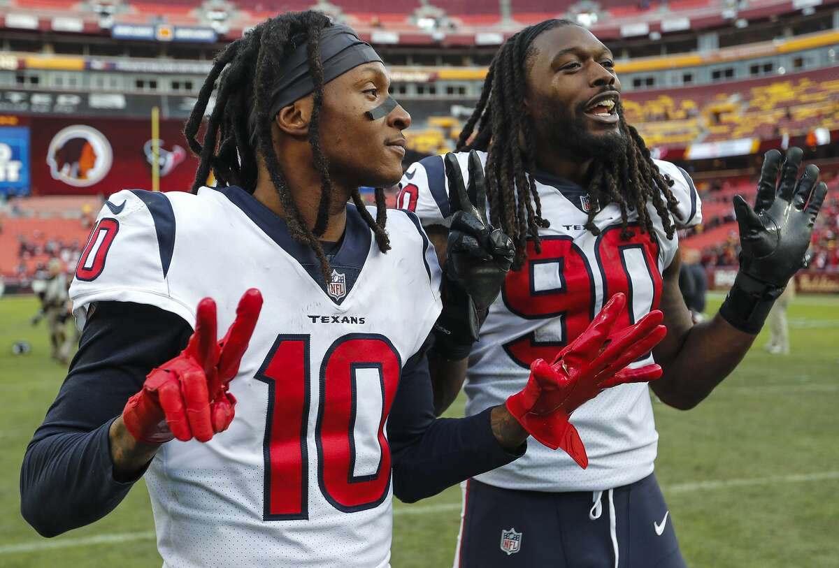 Houston Texans wide receiver DeAndre Hopkins (10) and outside linebacker Jadeveon Clowney (90) hold up seven fingers as they celebrate the Texans seventh straight win after beating Washington 23-21 at FedEx Field on Sunday, Nov. 18, 2018, in Landover, Md.