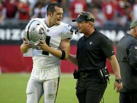 Oakland Raiders quarterback Derek Carr (4) talks with head coach Jon Gruden during the second half of an NFL football game against the Arizona Cardinals , Sunday, Nov. 18, 2018, in Glendale, Ariz. (AP Photo/Rick Scuteri)