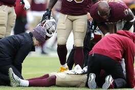 Washington quarterback Alex Smith (11) lies on the field after suffering a broken leg when he was sacked by Houston Texans strong safety Kareem Jackson and defensive end J.J. Watt during the third quarter of an NFL football game at FedEx Field on Sunday, Nov. 18, 2018, in Landover.
