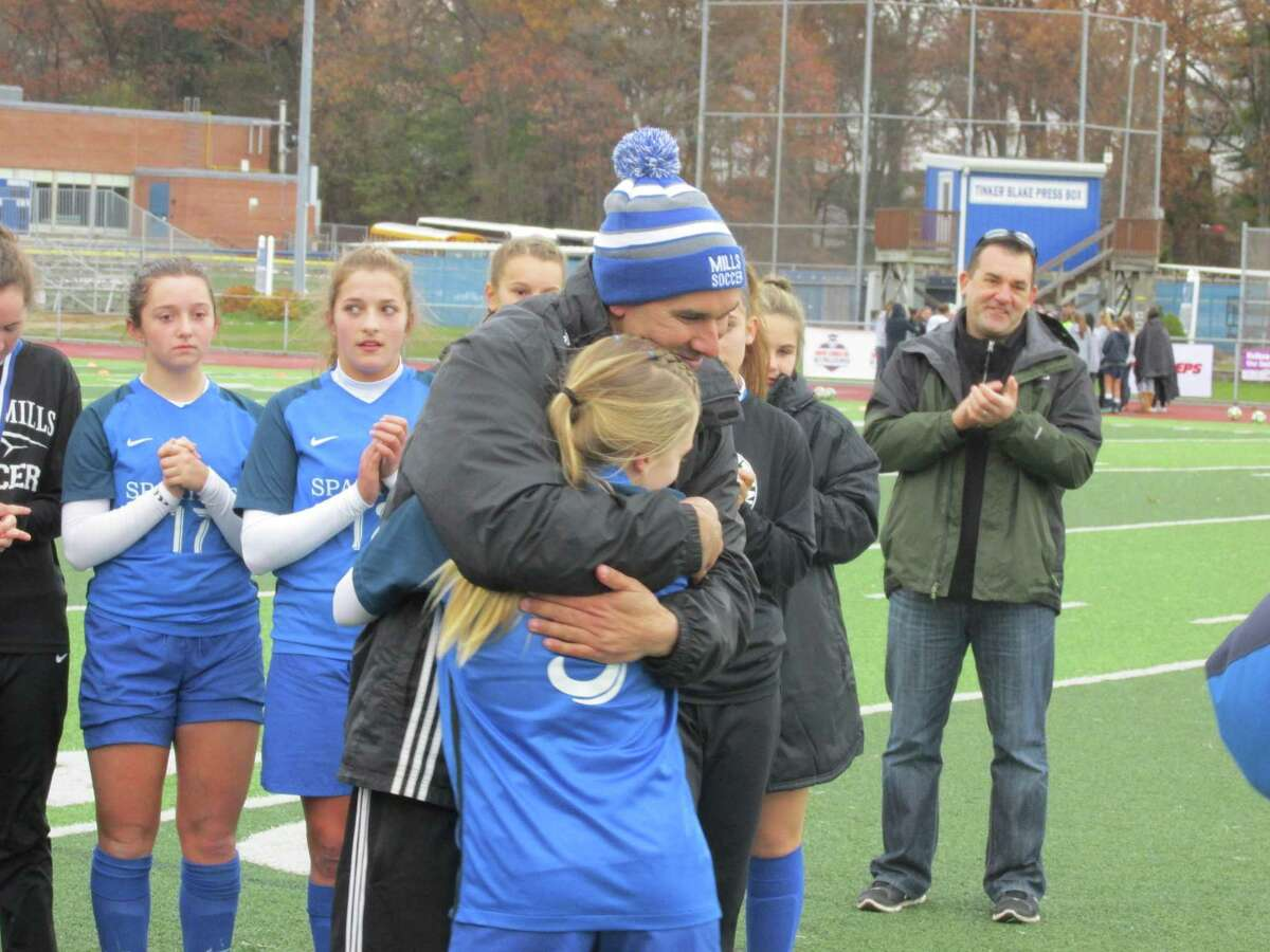 Lewis Mills coach Jared Sheikh congratulates Grace Buchanan after she was named MVP of the Class M State Tournament game at Ken Strong Stadium Sunday afternoon.