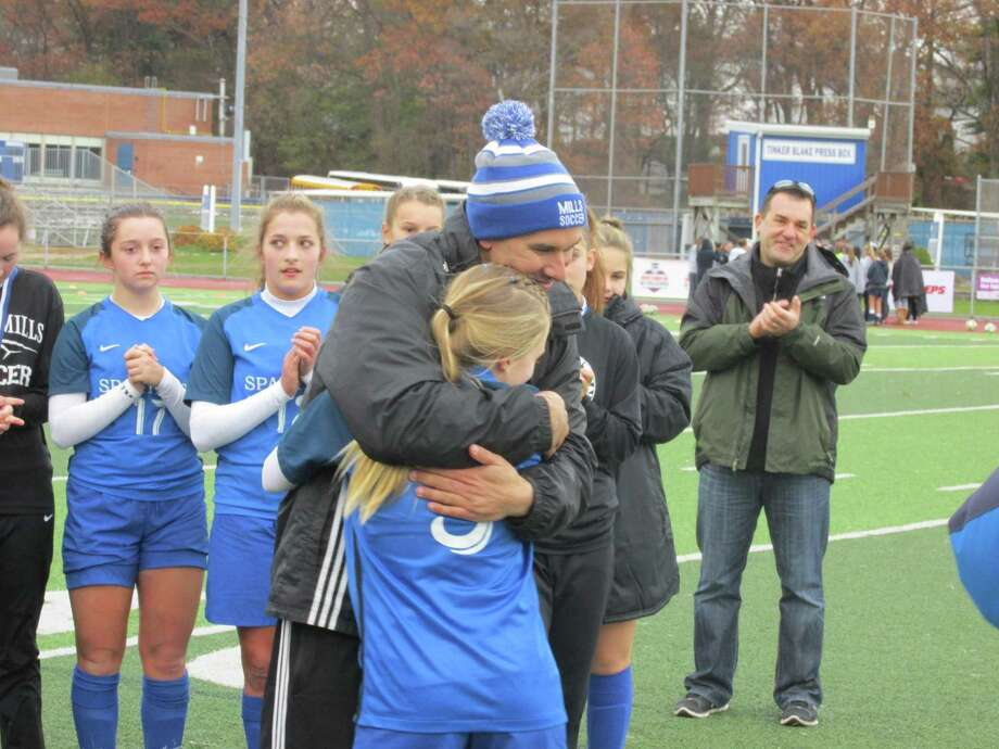 Lewis Mills coach Jared Sheikh congratulates Grace Buchanan after she was named MVP of the Class M State Tournament game at Ken Strong Stadium Sunday afternoon. Photo: Peter Wallace / For Hearst Connecticut Media