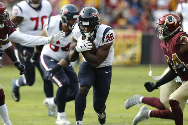 Houston Texans running back Lamar Miller (26) runs between Washington free safety Ha Ha Clinton-Dix (20) and cornerback Josh Norman (24) during the first quarter of an NFL football game at FedEx Field on Sunday, Nov. 18, 2018, in Landover, Md.