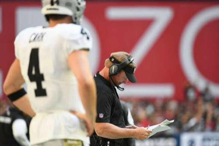 GLENDALE, AZ - NOVEMBER 18:  Head coach Jon Gruden of the Oakland Raiders looks to call a play as quarterback Derek Carr #4 stands on the sidelines in the NFL game against the Arizona Cardinals at State Farm Stadium on November 18, 2018 in Glendale, Arizona.  The Oakland Raiders won 23-21. (Photo by Jennifer Stewart/Getty Images)