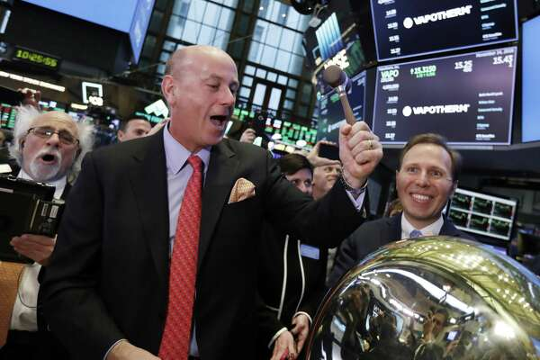 Vapotherm CEO Joe Army, center, and CFO John Landry, right, celebrate their company's IPO on the floor of the New York Stock Exchange, Wednesday, Nov. 14, 2018. (AP Photo/Richard Drew)