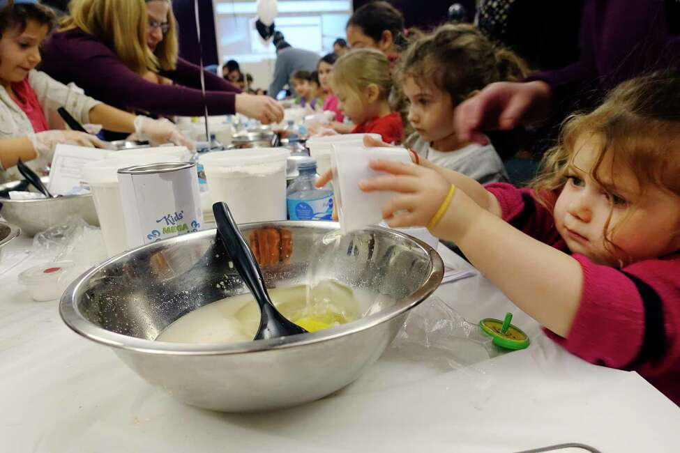 Sarah Rubin, 2, and her sister, Aidel Rubin, 4, background right, mix up the dough as they take part in the Kids Mega Challah Bake at the Albany JCC on Sunday, Nov. 18, 2018, in Albany, N.Y. At the event children learned how to mix, knead and shape their own traditional challah bread. The children made two loaves of challah, one for themselves and one to give to someone in need. The act of giving one loaf away is part of the teaching that God gives a little extra so that some of what we have can be given away to others in need. The event was organized by the Jewish Federation of Northeastern New York, Capital Chabad and PJ Library, and co-sponsored by Albany JCC, Congregation Beth Abraham Jacob, Congregation Beth Emeth, Hebrew Academy of the Capital District, and Maimonides Hebrew Day School. (Paul Buckowski/Times Union)