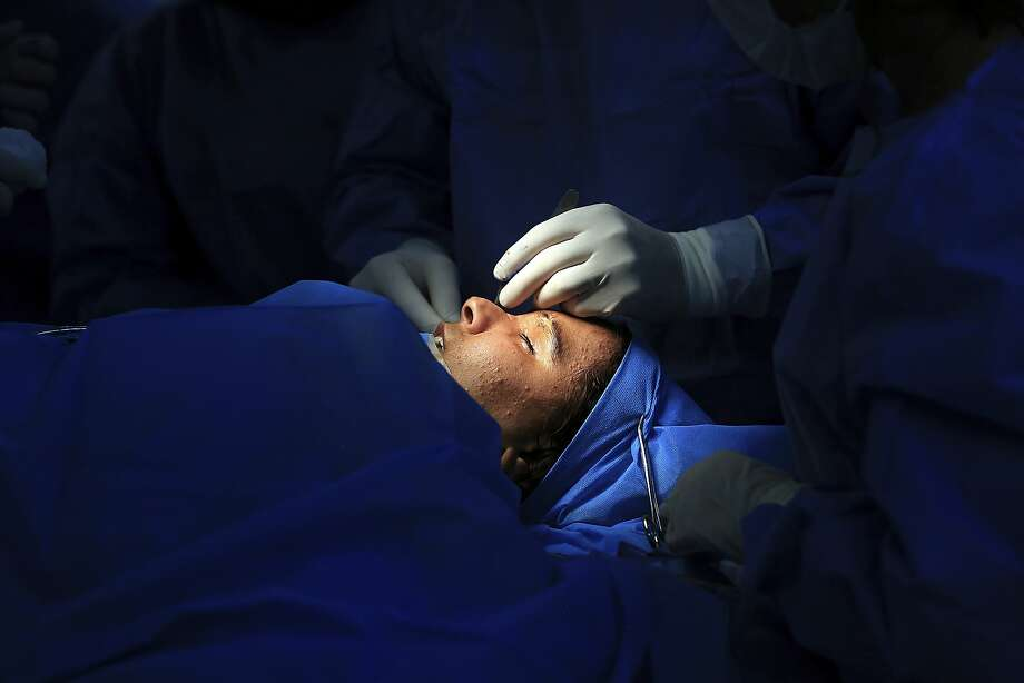 Plastic surgeon Abbas al-Sahan examines Saja Saleem on Nov. 6 in Baghdad. Saleem lost both eyes, her right arm and an ear in a bomb explosion in 2007. Al-Sahan answered an appeal she made on social media. Photo: Hadi Mizban / Associated Press