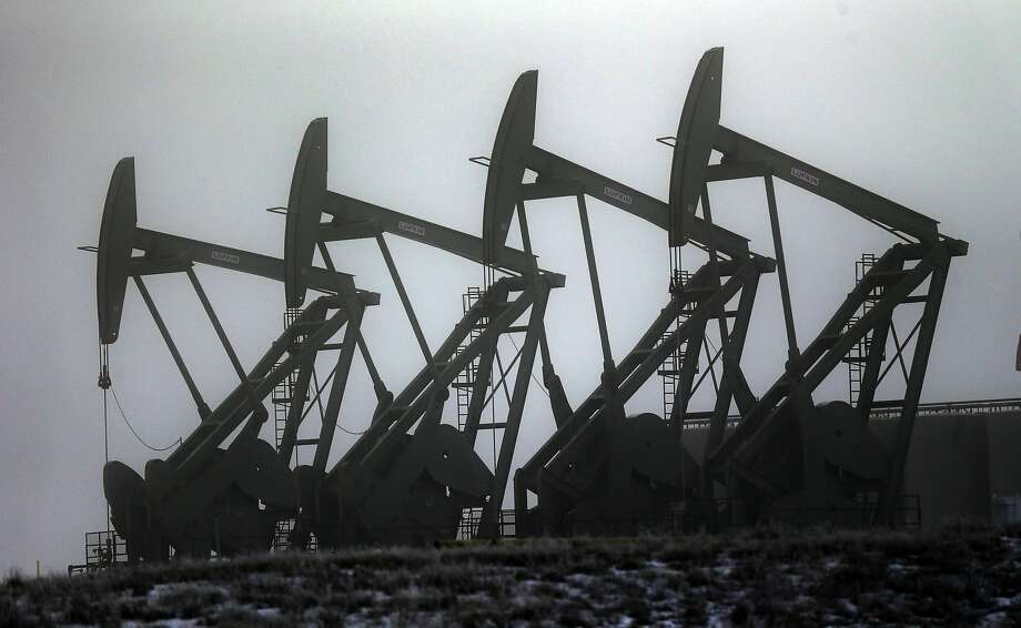 In this Dec. 19, 2014, file photo, oil pump jacks work in unison, in Williston, N.D.  Photo: Eric Gay, Associated Press