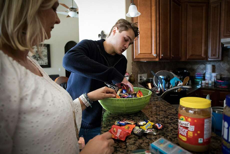 Carolee Grodi and her son, Carter, sort candy at home in Ocala, Fla. The treatment was transformative for Carter, making it easier to socialize and make plans to go away for college. Photo: Charlotte Kesl / New York Times