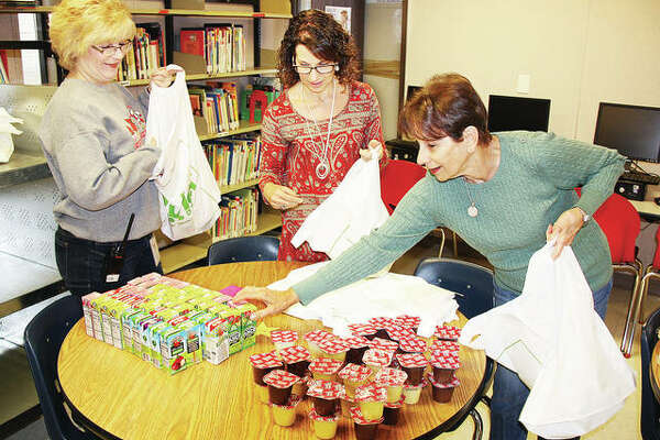 Gilson Brown Elementary School Assistant Brenda Kemper, left, Principal JoAnne Curvey and her mother, Lucille Haar, right, pack plastic bags with food as part of Project Third Day.