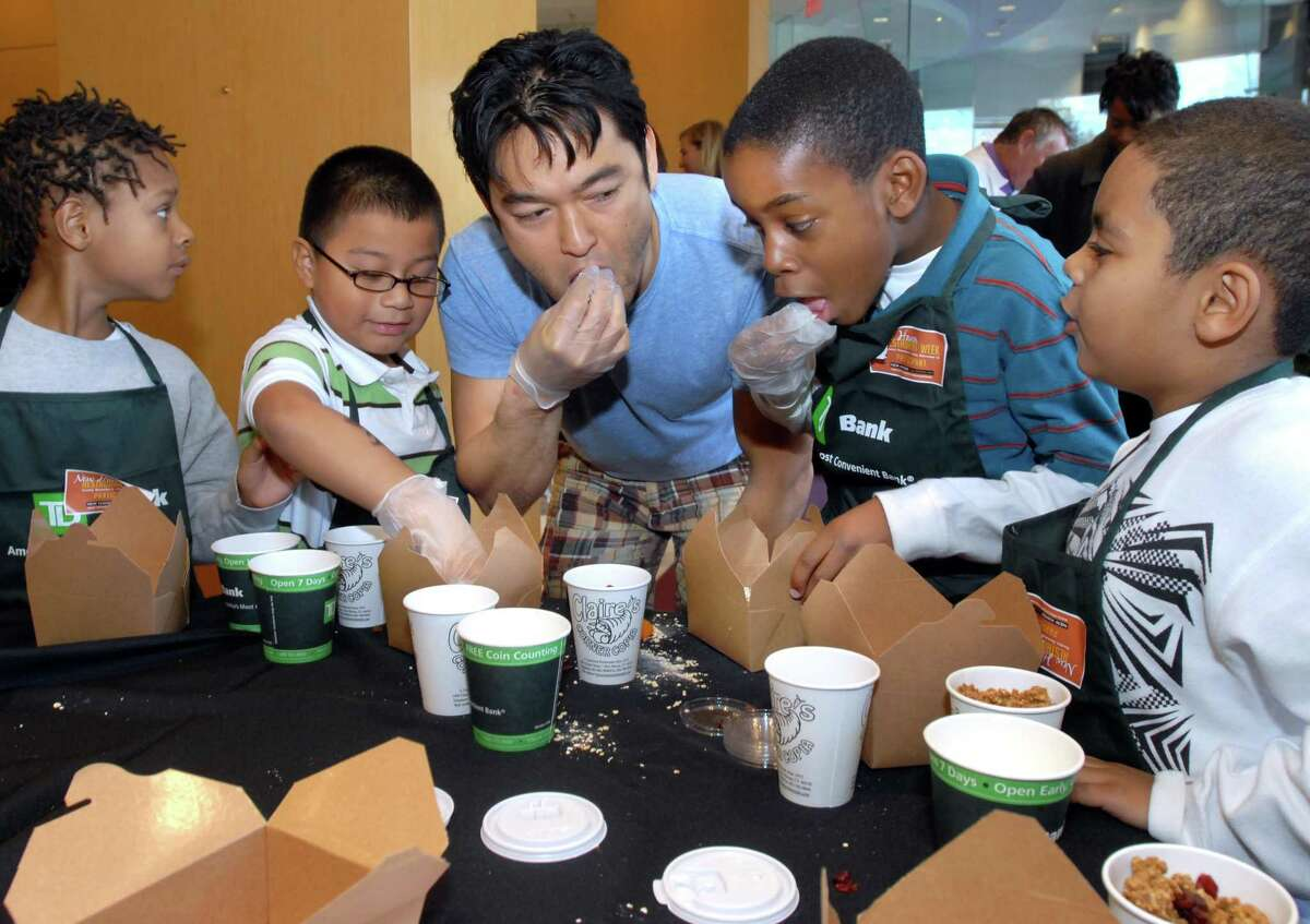 Five chefs participating in 2009 New Haven Restaurant Week showed second graders from Conte/West Hills Magnet School how to make a healthy snack - granola - at the TD Bank on Chapel Street. Bun Lai of Miya's Sushi center tastes their work with students.