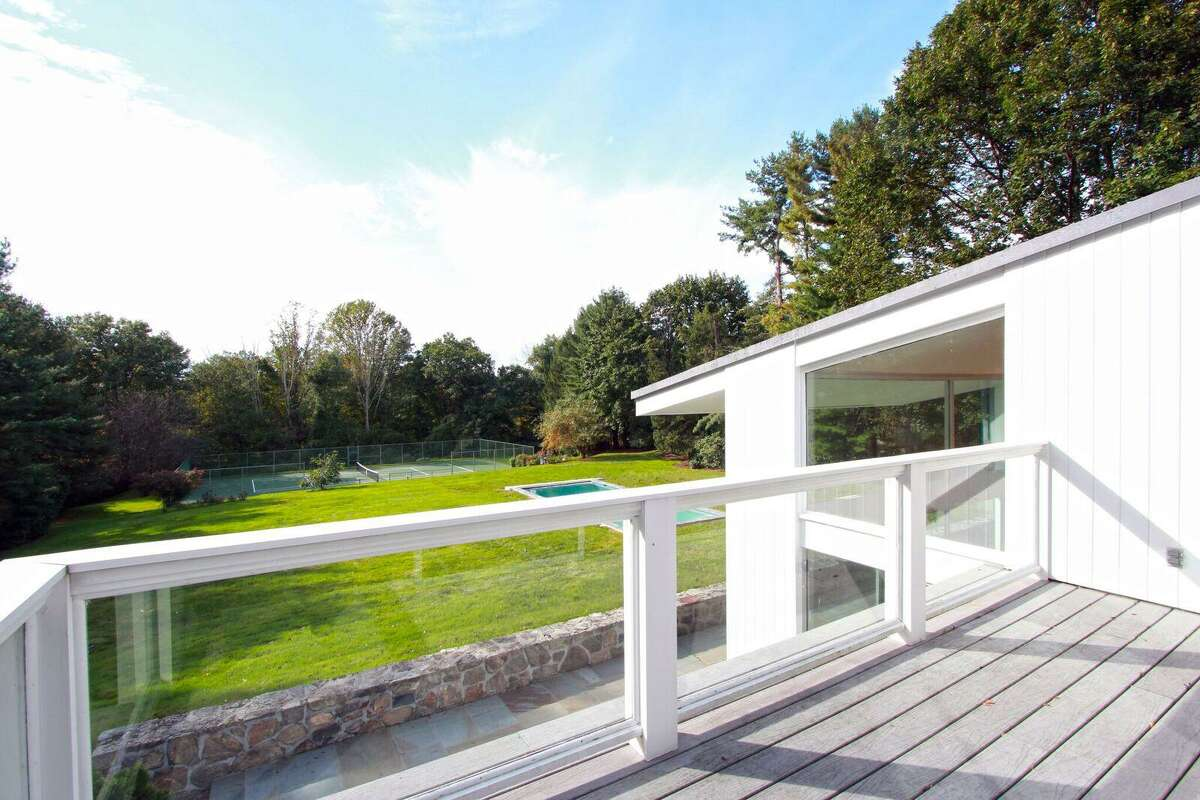 The private balcony accessed from the master bedroom suite looks over the private property, which is only about a mile from downtown New Canaan.