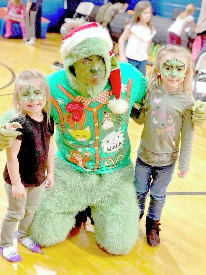 The Grinch (played by Ryan Brown) poses for a picture with some children attending Saturday's event. (Submitted Photo)
