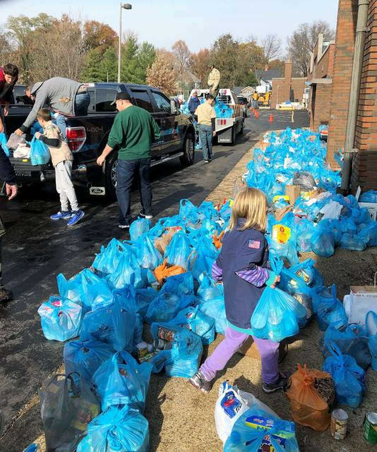"""Crews busy at work dropping off and picking up the """"blue bags"""" and delivering donations to Lincoln Middle School."""