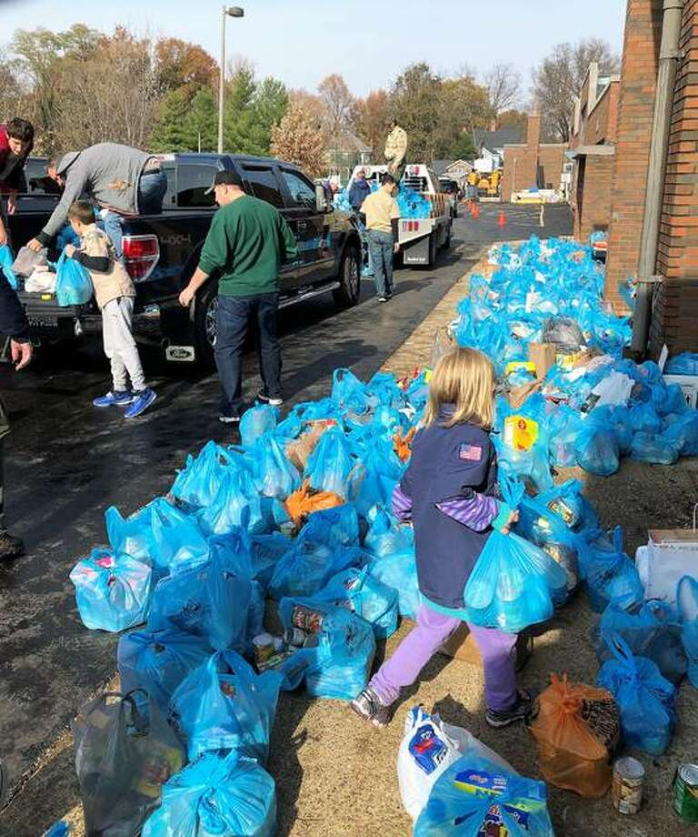 "Crews busy at work dropping off and picking up the ""blue bags"" and delivering donations to Lincoln Middle School. Photo: For The Intelligencer"