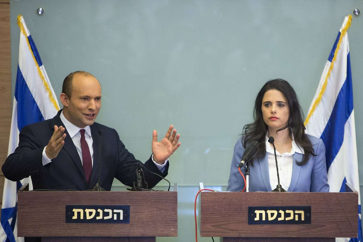 Israeli Education Minister Naftali Bennett, left, and Israeli Justice Minister Ayelet Shaked gesture as they speak during a press conference at the Knesset, Israel's parliament in Jerusalem, Monday, Nov. 19, 2018. Bennett, a senior coalition partner in Israel's government says he will not resign, averting early elections for now. (AP Photo/Sebastian Scheiner)
