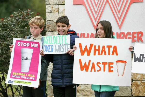Gustavo Metzger, 12, Emmanuel Perez, 12, and Isabel Perez, 12, join others holding signs outside Whataburger's San Antonio headquarters Monday.