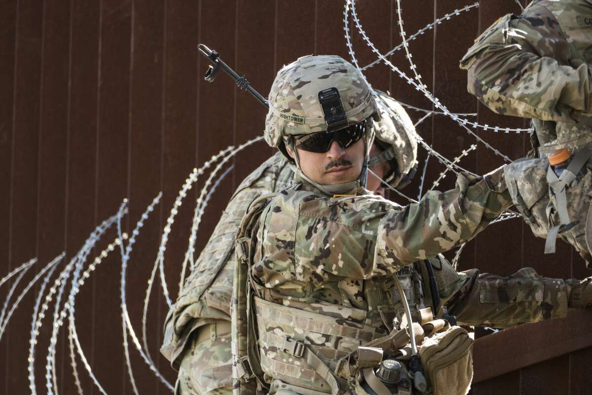 Soldiers of the 41st Route Clearance Company, 4th Engineer Battalion, who are currently based at Camp Donna, place concertina wire on a barrier at the McAllen-Hidalgo International Bridge on the U.S.-Mexico border on Friday, Nov. 16, 2018.