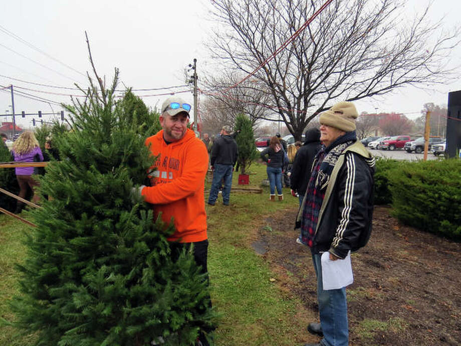 Darrell Gwinup, chairman of the tree committee for the Lion's Club, left, tells a volunteer where to place a tree Monday. Photo: Carol Arnett | The Intelligencer