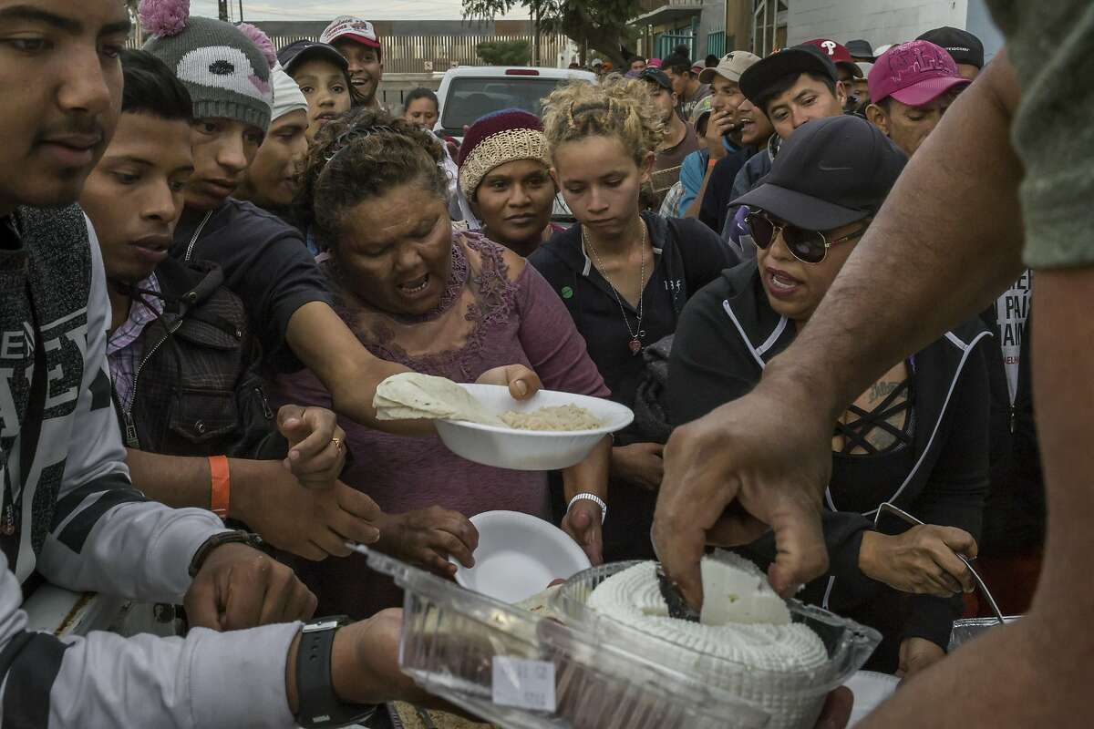 Migrants gather to receive food outside a shelter in Tijuana, Mexico, Nov. 17, 2018. As many as 10,000 Central Americans may reach Tijuana in the coming weeks. As the city scrambles to provide for them, a shelter has taken on the qualities of an overwhelmed refugee camp. (Mauricio Lima/The New York Times)