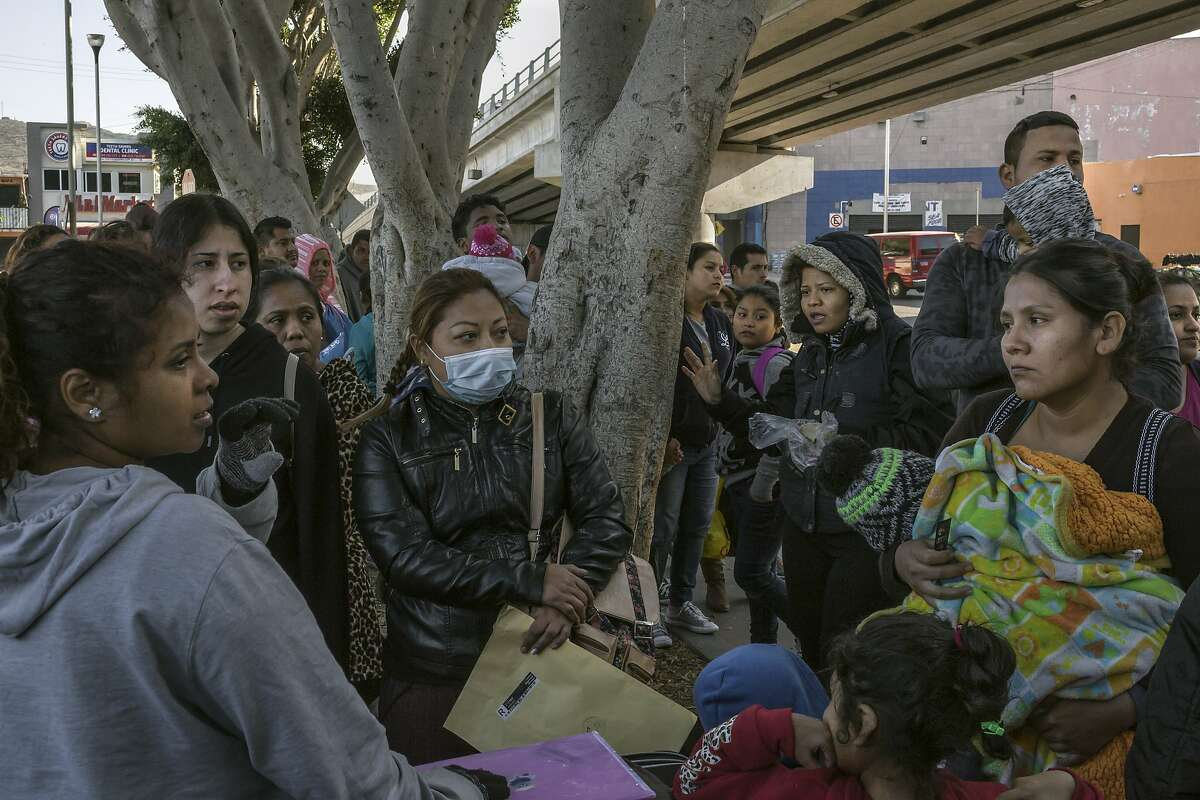 Mothers talk with each other after getting a number to apply for asylum, in Tijuana, Mexico, by the entrance to the border with the United States, Nov. 17, 2018. As many as 10,000 Central Americans may reach Tijuana in the coming weeks. As the city scrambles to provide for them, a shelter has taken on the qualities of an overwhelmed refugee camp. (Mauricio Lima/The New York Times)