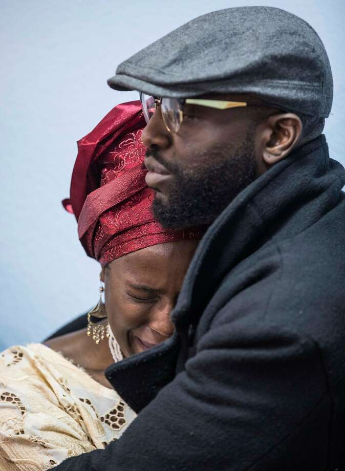 Ebele Okobi, sister of Chinedu Okobi, is comforted by her brother Tobenna. Photo: Jessica Christian / The Chronicle